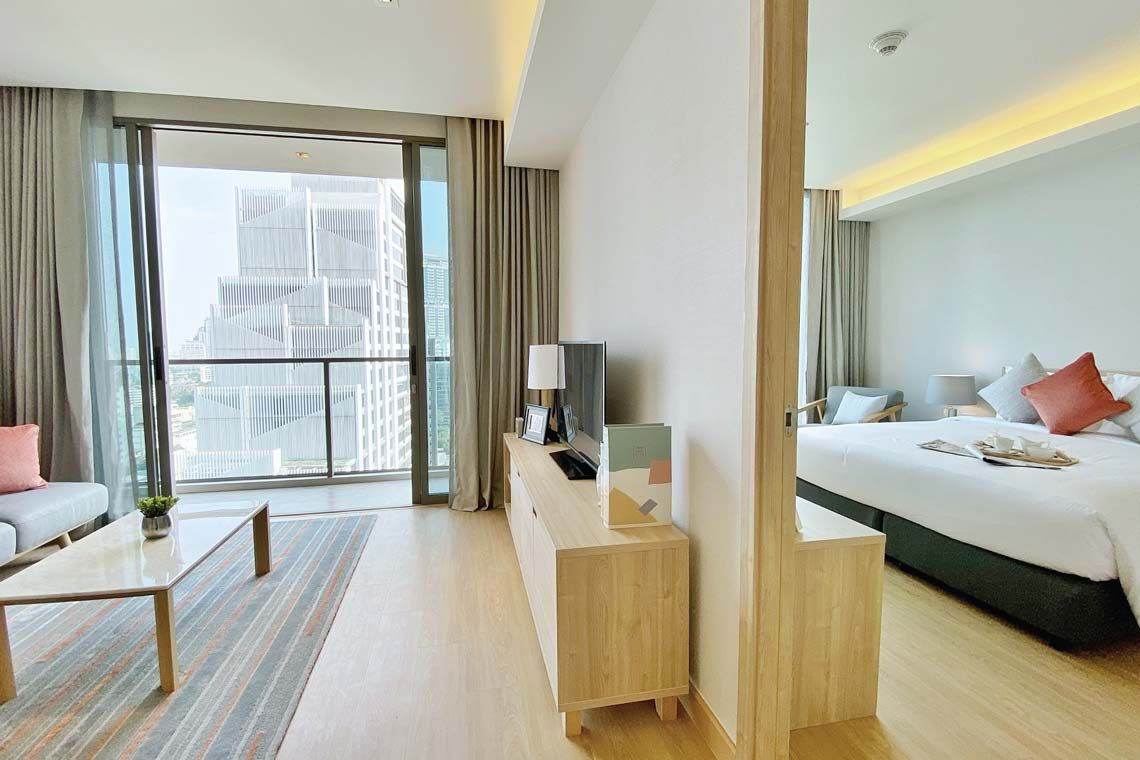 Oakwood Suites Bangkok's one-bedroom deluxe apartment's master bedroom and living room